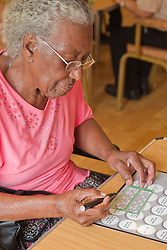 Elderly visually impaired woman playing bingo