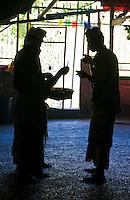 Men lighting incense inside the cave temple complex at Goa Giri Putri on Nusa Penida, Bali, Indonesia