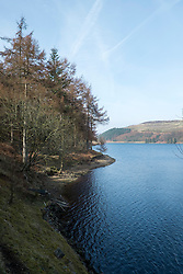 "The View north from the West bank of the Derwent Reservoir in Derbyshire, England is the middle of three reservoirs in the Upper Derwent Valley, the higher reservoir being Howden to the North and the lower being Ladybower to the south. Between them they provide practically all of Derbyshire's water, as well as to a large part of South Yorkshire and as far afield as Nottingham and Leicester.<br /> Begun in 1902 this neo-Gothic solid masonry dam wall is built from huge stones that were transported along a specially created railway from the quarries at Grindleford. Over 1,000 workers lived in a specially constructed and self-contained town of Birchinlee also known as ""Tin Town"". Derwent reservoir began being filled in November 1914, and overflowed for the first time in January of 1916. Covering an area of 70.8 hectares (175 acres) and at its deepest point is 34.7 metres (114 ft) the dam can support a total of 9.64 million cubic metres of water.<br /> For 6 weeks during the Second World War the reservoir was used by the pilots of the 617 Squadron ""the Dambusters"" to practice their low-level flying skills needed for Operation Chastise, because of the Derwents similarity to the operations German target. In for 2 weeks in 1954 the the sound of Lancaster bomber engines could be heard again over the Derwent as the reservoir stood in for the German dams a second time. This time for the filming of the ""The Dambusters"" starring Richard Todd as Guy Gibson. The west tower of the dam wall is home to Derwent Valley Museum and includes a permanent memorial to 617 Squadron to which is visible even when the Museum is closed. <br /> <br /> 22  March 2015 Image © Paul David Drabble www.pauldaviddrabble.co.uk"