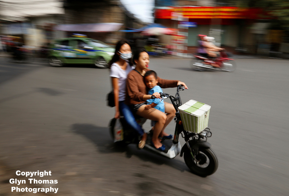 Three people traveling on a moped in Hanoi, Vietnam