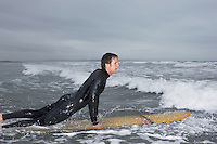 Surfer pulling himself up onto surfboard in water side view