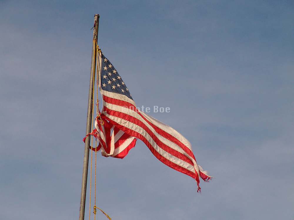 An old ripped American flag against the sky.