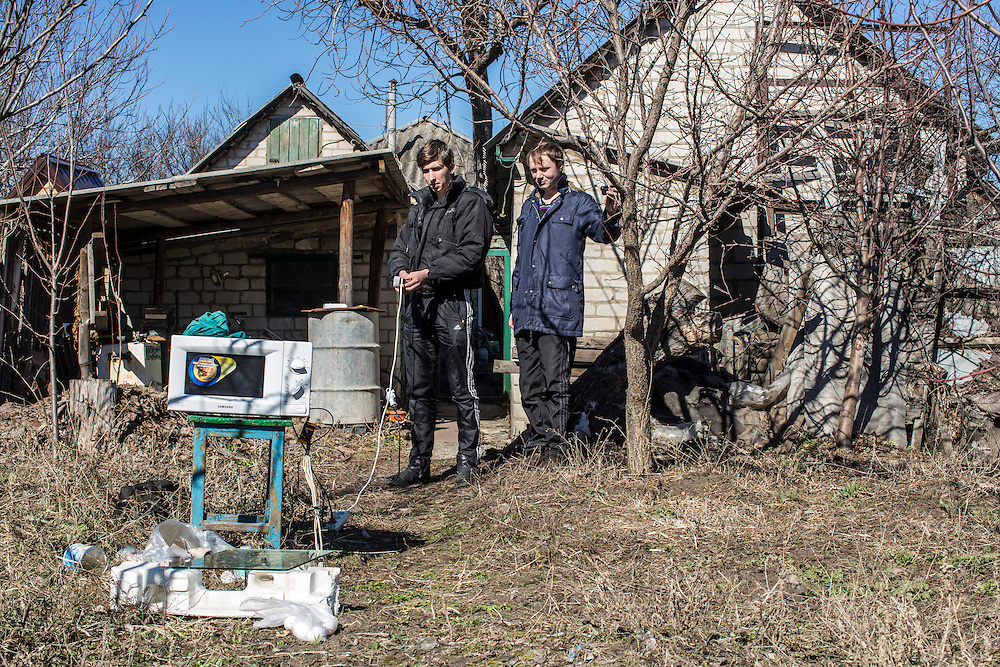 LUHANSK, UKRAINE - MARCH 16, 2015: Pavel Pavlov, left, and Aleksandr Kryukov conduct a scientific experiement involving microwaves in the yard of the house where Kryukov lives with his grandmother in Luhansk, Ukraine. The two have created a series of popular YouTube videos involving scientific experiements. CREDIT: Brendan Hoffman for The New York Times