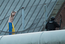 © Licensed to London News Pictures . 13/09/2015. Manchester, UK. An inmate at HMP Manchester ( Strangeways Prison ) , named as STUART HORNER , climbs netting and protests conditions inside . Photo credit : Joel Goodman/LNP