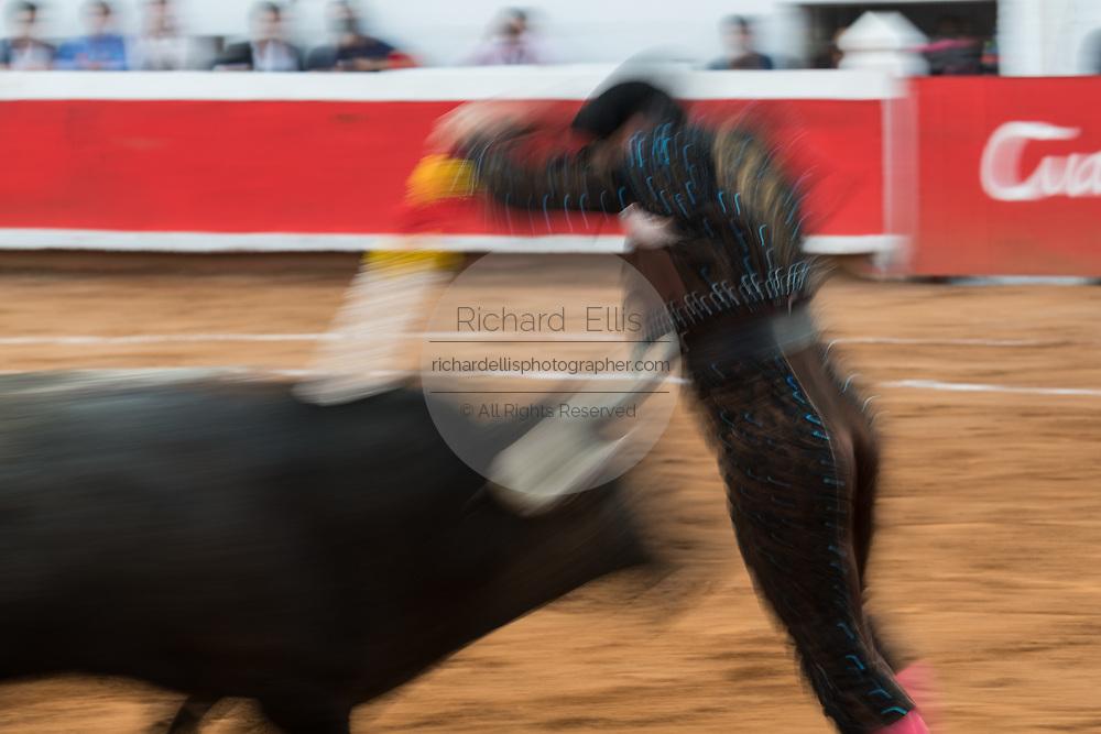 A show shutter shows the action as Mexican Matador thrusts banderillas into a bull during a bullfight at the Plaza de Toros in San Miguel de Allende, Mexico.