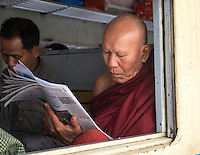 YANGON, MYANMAR - CIRCA DECEMBER 2013: Monk reading newspaper while awaits train to depart from Yangon Central Railway Station