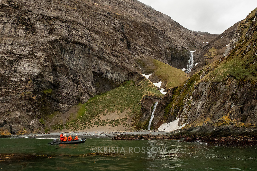 People on a zodiac cruise look at a waterfall while on an exploration at Hercules Bay on the north coast of South Georgia Island.