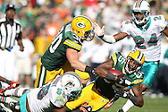 GREEN BAY, WI - OCTOBER 17: Greg Jennings #85 of the Green Bay Packers is tackled by Karlos Dansby #58 of the Miami Dolphins at Lambeau Field on October 17, 2010 in Green Bay, Wisconsin. The Dolphins defeated the Packers 23-20 in overtime. (Photo by Tom Hauck) Player:Greg Jennings;  Karlos Dansby