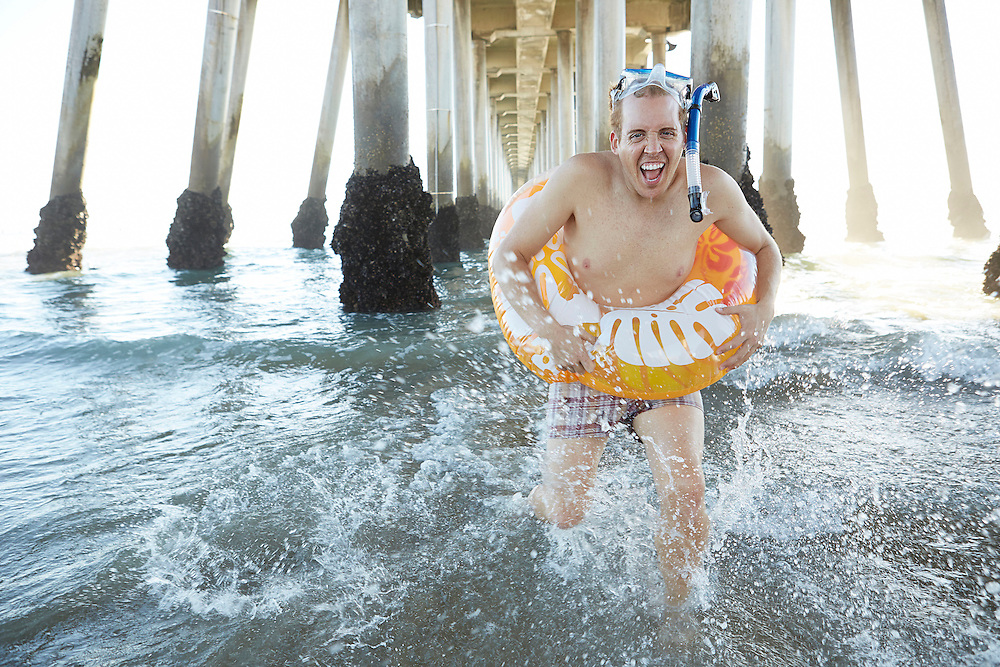 Lifestyle image of guy with donut pool float and goggles running in ocean under pier