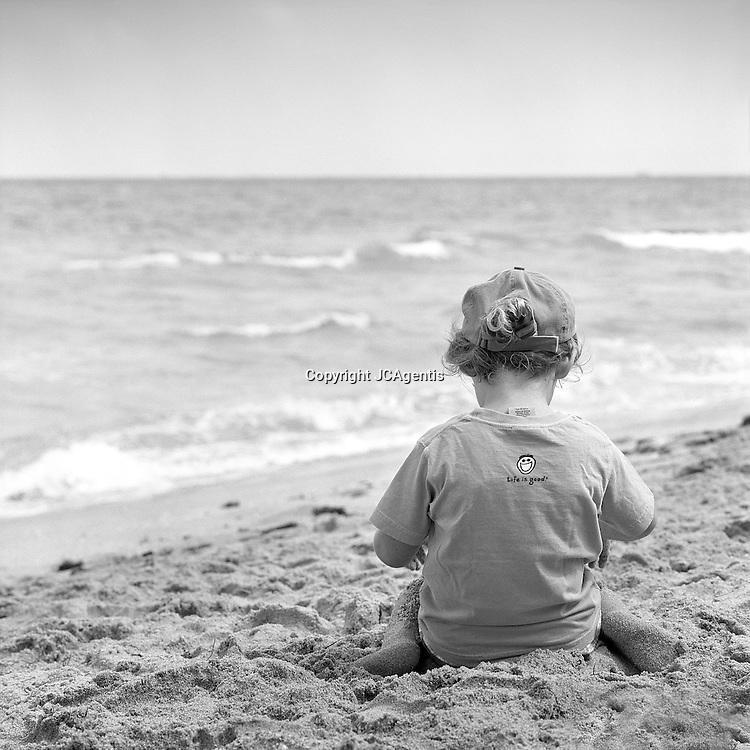Serene touching seascape of Child playing on beach before the ocean in black and white B&W