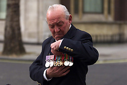 Ron Moore adjusting his medal. Ron was an air gunner in 1943 -1946, during the 60th Anniversary service of The Commonwealth Air Plan, The St Clement Danes church, Strand, London, April 30, 2000. Photo by Andrew Parsons / i-images..