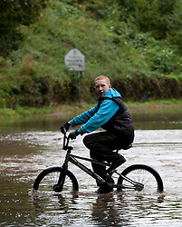 © Licensed to London News Pictures.24/09/2012. Solihull,West Midlands. A young boy tries to cross a flooded Aquaduct Lane on his bike in Majors Green, Solihull, West Midlands. Photo credit : Dave Warren/LNP