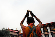 Devout pilgrims prostrate themselves thousands of times in their arduous quest for enlightenment.<br /> <br /> Each day during Losar (Tibetan New Year),thousands of pilgrims walk the kora around the Jokhang temple and the Potala Palace.