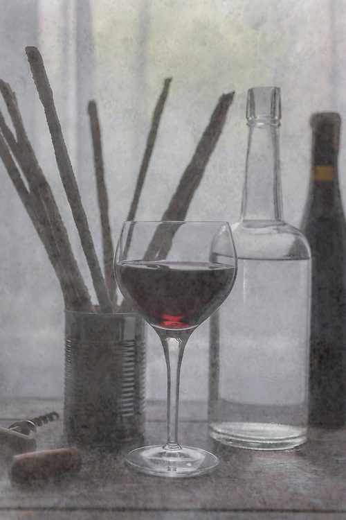 """A still life image of a basic Italian table setting. Red wine, breadsticks and water sit on a table by a window sheer. I was inspired by the old, famous oil painting called 'Grace"""". This would look nice in a kitchen, dining area or a bar."""