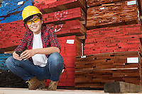 Portrait of an Asian female industrial worker holding cell phone with stacked wooden planks in background