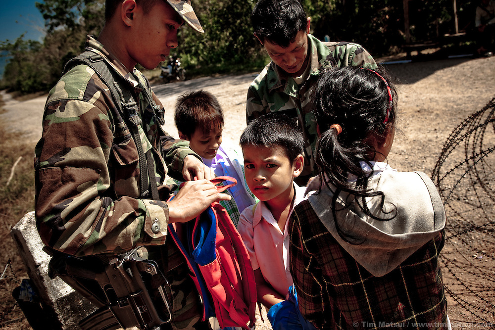 """Thai military at the Thai border examine school children's book bags for drugs or other contraband. Border guards say children of Cambodians living and working in the Thai border town of Klong Yai often pass through the heavily mined """"White Zone"""" between the two countries to attend school in Cambodia to maintain their language and culture"""