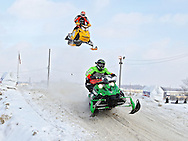 Rob Keeling (front) of Ames lands as Mike Hudecek (top) of Maynard gets some air at the Frozen Few 1st Inaugural Amateur Sno-X Race held at Hawkeye Downs, 4400 6th Street SW in Cedar Rapids on Saturday January 22, 2011. 1,200 people turned out to watch over 50 racers in 12 divisions at the event sponsored by the Frozen Few Snowmobile Club. A portion of the proceeds went to the Spina Bifida Association of Iowa. The next race is February 19th.