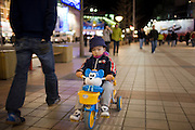 Boy rides a tricycle on Wangfujing Street, Beijing. China has a one child family planning policy to limit population.