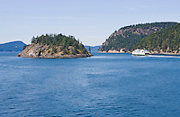 A washington State ferry cruises between two islands in the San Juan Islands of Washington State, USA.