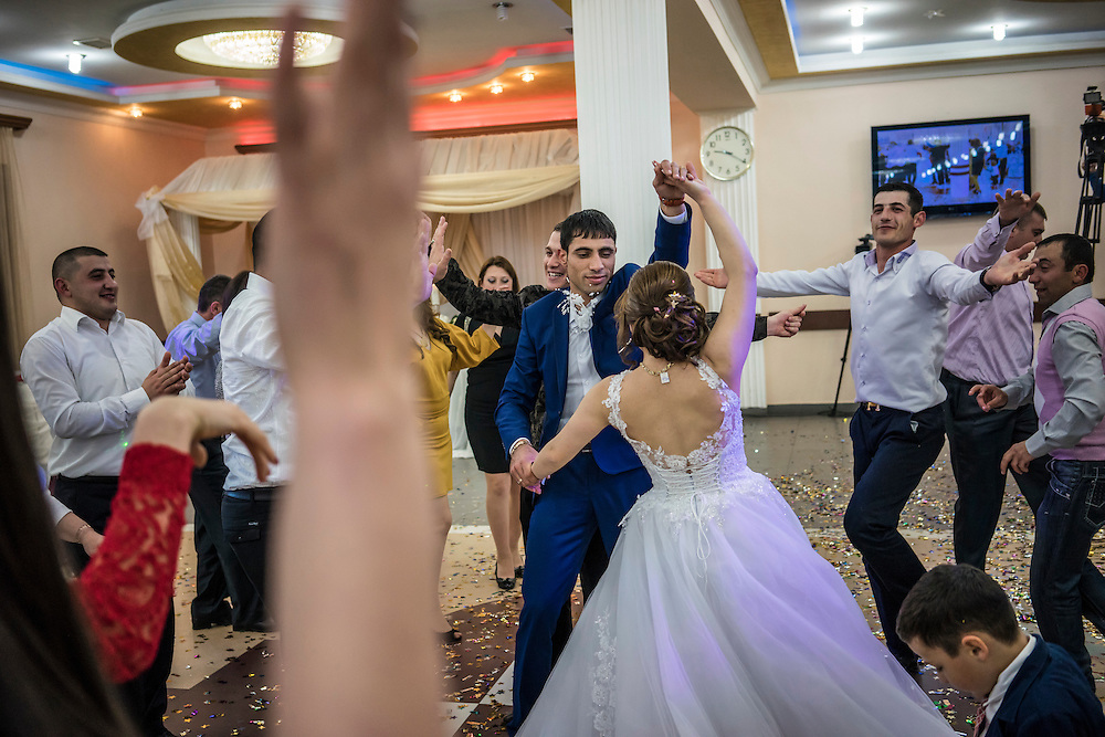 STEPANAKERT, NAGORNO-KARABAKH - APRIL 18: Groom Davit Simonyan, 24, and bride Shogher Hovsepyan, 25, dance at their wedding reception on April 18, 2015 in Stepanakert, Nagorno-Karabakh. Since signing a ceasefire in a war with Azerbaijan in 1994, Nagorno-Karabakh, officially part of Azerbaijan, has functioned as a self-declared independent republic and de facto part of Armenia, with hostilities along the line of contact between Nagorno-Karabakh and Azerbaijan occasionally flaring up and causing casualties. (Photo by Brendan Hoffman/Getty Images) *** Local Caption *** Davit Simonyan;Shogher Hovsepyan