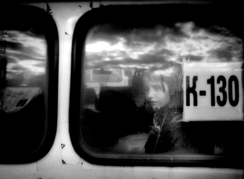 Girl Gazes from Back Window of Minibus, near St. Petersburg, Russia.