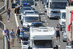 &copy; Licensed to London News Pictures. 23/07/2016<br /> People standing on the M20 WAITING  FOR THE TRAFFIC TO MOVE.<br /> M20 traffic near the Euro Tunnel Service Station at the back of a very very long queue into Dover, kent.<br /> Dover bound traffic ON THE  M20 in Kent at Junction 11A AND 12.  Queueing traffic because of very long delays at French border contol. <br /> <br /> <br /> (Byline:Grant Falvey/LNP)