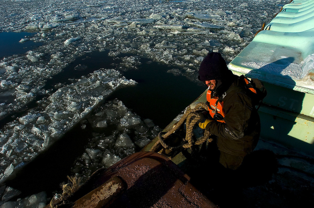 Trumble River Service deckhand Bill Beard handles rope as ice clogs the Illinois River below. ©David Zalaznik