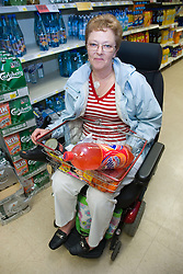 Older woman wheelchair user shopping for food in a supermarket,