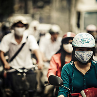 Masks are commonly worn when riding through the dirty air during rush hour in Saigon