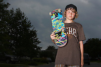 Teenage boy holding skateboard standing on street low angle view portrait