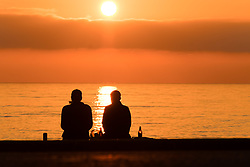 © Licensed to London News Pictures.29/03/2019. Aberystwyth, UK. A couple of people enjoying an evening drink on the promenade in Aberystwyth, on the Cardigan Bay coast of west Wales are silhouetted by the flaming setting sun . High pressure continues to dominate the weather for much England and Wales, with settled conditions forecast to last at least another day , before more cooler conditions return. Photo:Keith Morris/LNP