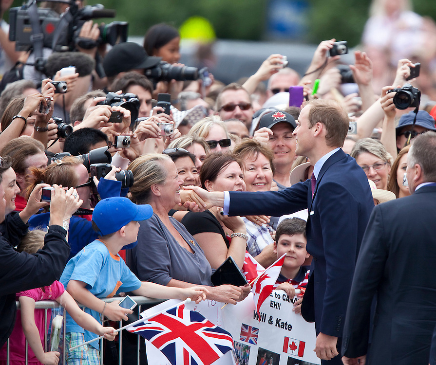 Prince William greets well wishers following a wreath laying ceremony at the National War Memorial in Ottawa, Ontario, June 30, 2011, the first stop on his nine-day tour of Canada with his wife Catherine  the Duchess of Cambridge, their first official foreign trip as husband and wife.<br /> AFP PHOTO/GEOFF ROBINS