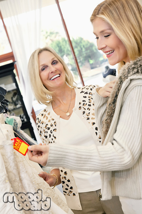 Cheerful mother and daughter looking at price tag of wedding gown in bridal store