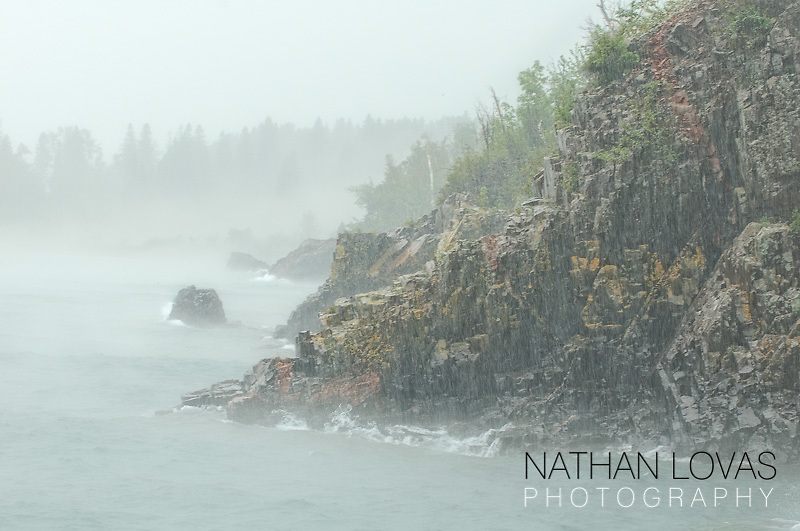 Rock out-cropping on Lake Superior shoreline with fog and rain; Minnesota.