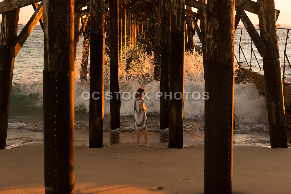 Young Girl on the Beach Under the Seal Beach Pier at Sunset
