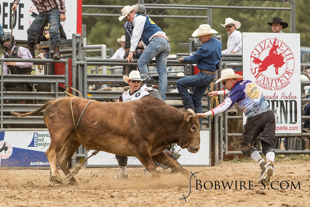 Bullfighters Nate Jestes (light shirt) and Cade Burns come to the aid of bull rider Elijah Mora after his ride on Summit Pro Rodeo's Circus Mouse during the third performance of the Elizabeth Stampede on Sunday, June 3, 2018.