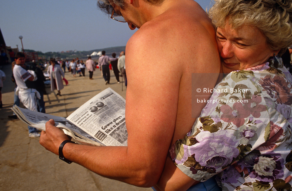A wife gives an tight, affectionate hug to her husband on the Promenade at North Bay, Scarborough, North Yorkshire. There is no such showing of reciprocated love from the man who continues to read a cricket report in the sports page of his tabloid newspaper. She is wearing a floral summer top and he is topless. In the background we see a bustling sea front. People are walking along the Prom, enjoying the sun and warmth of this usually chilly area of Britain.