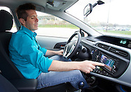 Edward Moran of Ames shows the various functions of the display inside his new Toyota Prius C in Ames, Iowa on Thursday, March 29, 2012.