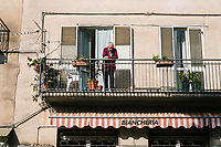 """PISCIOTTA, ITALY - 22 APRIL 2018: An elderly man is seen here on his balcony in Pisciotta, Italy, on April 22nd 2018.<br /> <br /> Former restaurant owners Donatella Marino and her husband Vittorio Rimbaldo have spent the recent years preparing and selling salted anchovies, called alici di menaica, to a growing market thanks to a boost in visibility from the non-profit Slow Food.  The ancient Menaica technique is named after the nets they use brought by the Greeks wherever they settled in the Mediterranean. Their process epitomizes the concept of slow food, and involves a nightly excursion with the special, loose nets that are built to catch only the larger swimmers. The fresh, red anchovies are immediately cleaned and brined seaside, then placed in terracotta pots in between layers of salt, to rest for three months before they're aged to perfection.While modern law requires them to use PVC containers for preserving, the government recently granted them permission to use up to 10 chestnut wood barrels for salting in the traditional manner. The barrels are """"washed"""" in the sea for 2-3 days before they're packed with anchovies and sea salt and set aside to cure for 90 days. The alici are then sold in round terracotta containers, evoking the traditional vessels that families once used to preserve their personal supply.<br /> <br /> Unlike conventional nets with holes of about one centimeter, the menaica, with holes of about one and half centimeters, lets smaller anchovies easily swim through. The point may be to concentrate on bigger specimens, but the net also prevents overfishing."""