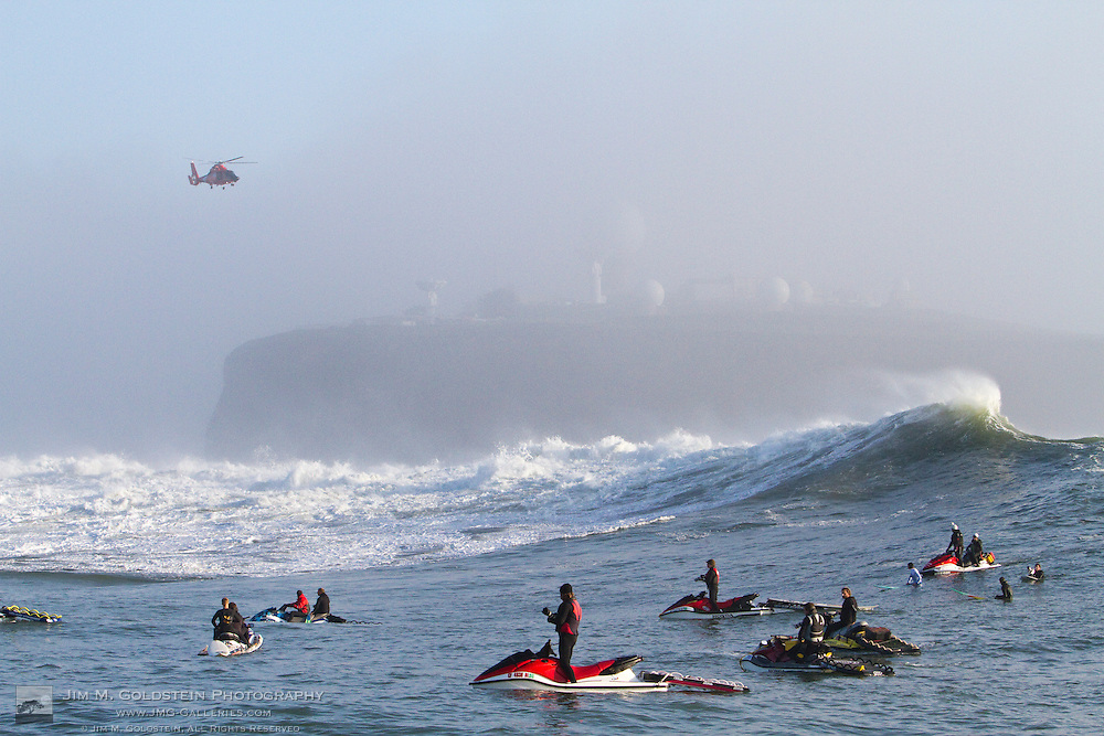 """A Coast Guard H-65 """"Dolphin"""" helicoptor hovers over crashing waves at the Mavericks Surf Contest held in Half Moon Bay, California on February 13, 2010"""