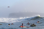 "A Coast Guard H-65 ""Dolphin"" helicoptor hovers over crashing waves at the Mavericks Surf Contest held in Half Moon Bay, California on February 13, 2010"