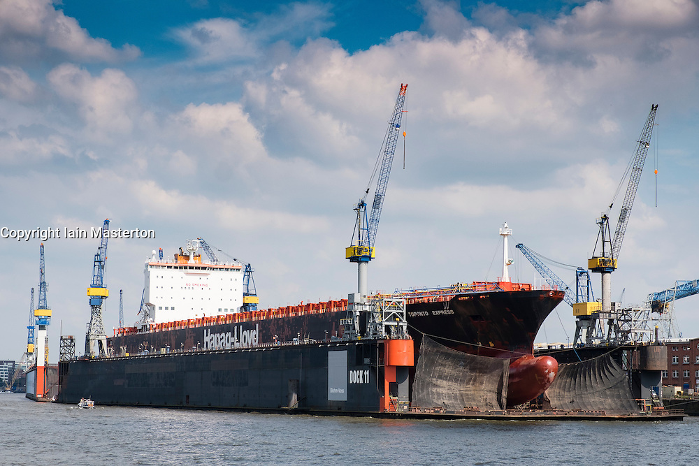 Container ship undergoing repairs in dry dock at  Port of Hamburg on River Elbe in Germany