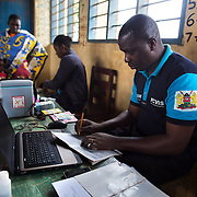 Data clerk Oscar Kai (blue shirt), at the Ngamani Primary School for an outreach health clinic. Oscar will enter data about the PCV 10 vaccine, as well as pentavalent, BCG, polio, yellow fever, measles, diphtheria, tetanus and hepatitis B immunizations. All of that fresh information is then uploaded to portable hard-drives that are returned weekly to the study headquarters, where the database is updated.<br /> <br /> &quot;Because the database is digitized, it means it's far easier to keep our records fresh, even if children move and access health services in different locations,&quot; says Dr. Benjamin Tsofa, the Kenyan health ministry's chief liaison on the study. <br /> <br /> In January 2011, the Kenyan government with support from the GAVI Alliance, introduced a new vaccine, PCV-10, which targets 10 bacteria than can cause Invasive Pneumococcal Disease.The vaccine's impact is monitored through an electronic database, part of the GAVI funded PCV impact study, which maps the growing coverage of the new vaccine. Already, here in Kilifi, the incidence of the illness in children aged five has gone down by approximately two-thirds.