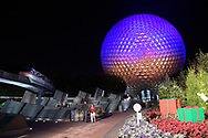 Guests walk in front of the Spaceship Earth ride at the entrance to the Epcot theme park, as a monorail passes overhead, at the Walt Disney World Resort in Lake Buena Vista, Fla., Wednesday, Dec. 14, 2016. (Phelan M. Ebenhack via AP)
