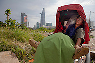 A cyclo driver sleeping in his cyclo parked along a waste land. Bitexco tower in background contrasts with the unspoiled area. Ho Chi Minh city, Vietnam, Asia