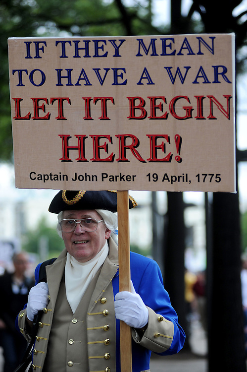 """Robert Chamberlain, of North Carolina, walks along the sidewalk in costume as a crowd marches down Pennsylvania Ave. to the U.S. Capitol to have thier voices heard during the Tea Party Protest on Sept. 12, 2009 in Washington, DC. """"We have to stop big government spending,"""" said Chamberlain."""