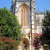 Batalha Monastery Main Portal in Batalha, Portugal<br /> In appreciation for winning the Battle of Aljubarrota and becoming the King of Portugal in the late 14th century, John I formed the town of Batalha (which means battle) and commissioned the Monastery of Santa Maria de Vitória in praise to St. Mary for his victory.  Below the gorgeous lattice window is an archivolt over the main portal that contains 78 delicate Biblical carvings.