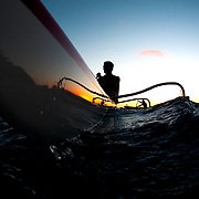Outrigger canoers Jimmy Austin and Keizo Gates paddling at sunset near China Walls on Eastern Oahu near Honolulu, Hawaii.