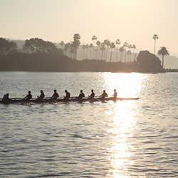 Photo of boat rowing team in Newport Bay (Newport Harbor) in Newport Beach California with Corona Del Mar in the background. Photo was taken at the end of Balboa Peninsula where Newport Bay meets the Pacific Ocean. Newport Beach is a beach community along the Pacific Ocean in Orange County Southern California.