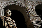 Low angle view of a Roman statue of Minerva in the Central Patio, Casa de Pilatos (Pilate's House), Seville, Spain, pictured on December 30, 2006, in the afternoon. Pilate's House, late 15th century, was built by the Enriquez and Ribera families During the 16th century these families, who had a strong relationship with Italy,  introduced the Renaissance style to Seville. In the palace is the sculpture collection of the Duke of Alcala  who brought back many Classical pieces from Italy and adapted the palace and gardens to exhibiting them in Renaissance style. The buildings were further modified according to Romantic taste in the 19th century and now present a combination of Mudejar-Gothic, Renaissance and Romantic styles. Today the Casa de Pilatos belongs to the Fundacion Casa Ducal de Medicaneli and is the residence of the Dukes of Medicaneli. Picture by Manuel Cohen.